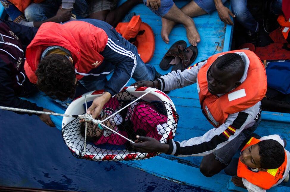 Immigrati che calano un neonato su un barcone