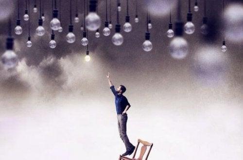 Uomo che cerca di raggiungere lampadine che pendono dal soffitto
