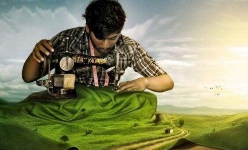Uomo con una macchina da cucire mentre costruisce il suo successo