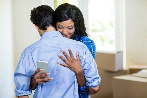 Donna guarda il telefono mentre abbraccia il fidanzato
