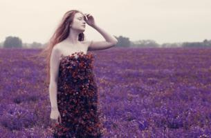 Ragazza in un campo di fiori viola che vive momenti difficili