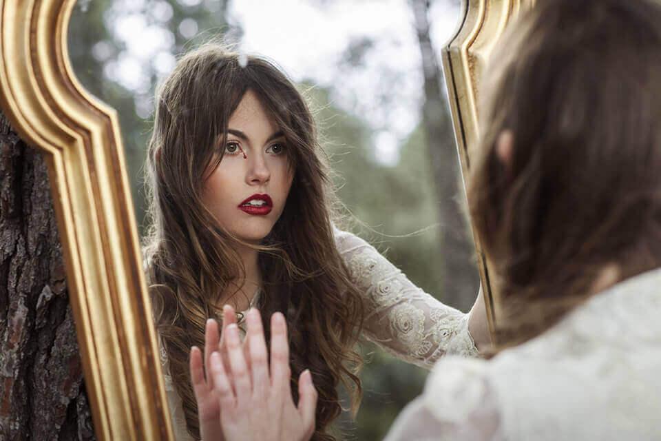 Ragazza si guarda allo specchio mentre piange lacrime di sangue
