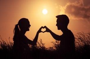 Uomo e donna che fanno un cuore con le mani