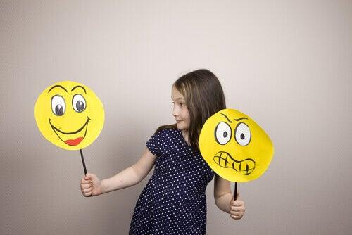 Bambina che tiene due facce disegnate