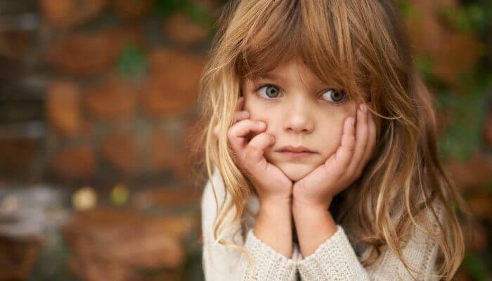 Bambina con la faccia tra le mani