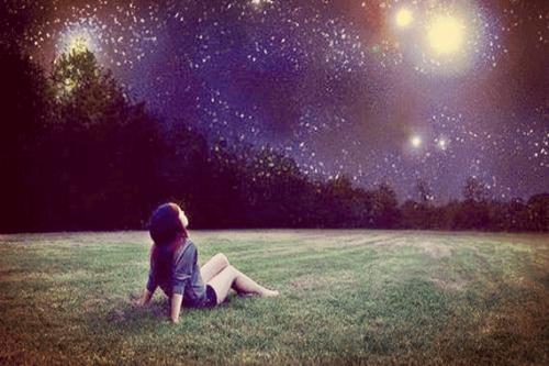 Bambina seduta sull'erba che guarda il cielo e scopre la sua stella
