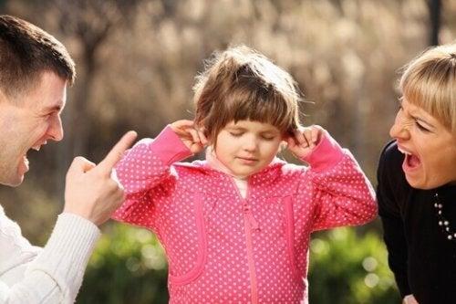 Bambina che si tappa le orecchie mentre è in mezzo ai suoi genitori che le gridano contro