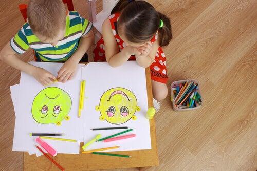 Bambini che disegnano dei volti con varie espressioni ed emozioni, in rappresentazione dell'alfabetizzazione emotiva