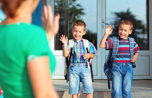 Mamma che saluta figli che vanno a scuola