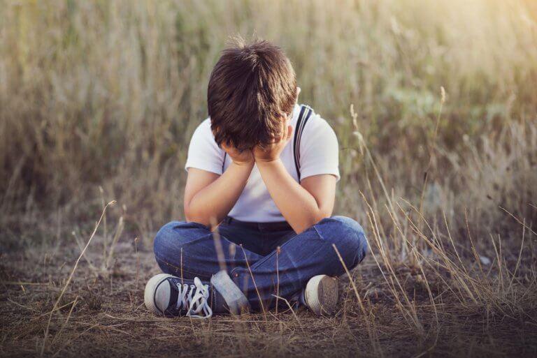 Bambino seduto a terra che piange