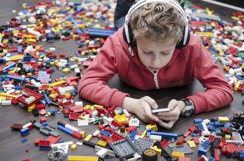 Bambino con lego attorno e smartphone