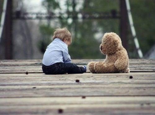 Bambino seduto con il suo orsacchiotto