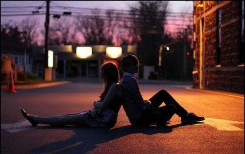 Una coppia giovane seduta in strada