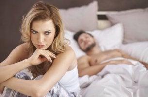 Donna a letto preoccupata per la anorgasmia femminile