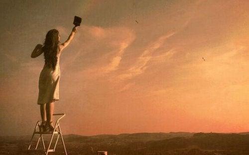 Donna dipinge il cielo, mostrando che la depressione se ne va