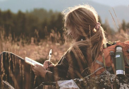 Donna che scrive una lettera all'aperto