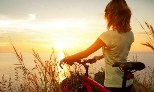 Donna con bicicletta mentre guarda l'alba e si sente motivata