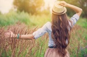 Donna con cappello che cammina in un prato
