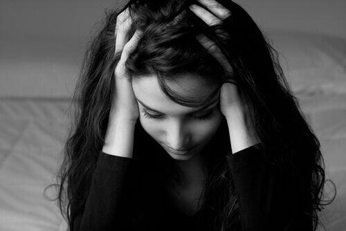 Donna con le mani tra i capelli perché prova mom shaming