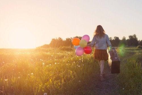 Ragazza con palloncini e valigia