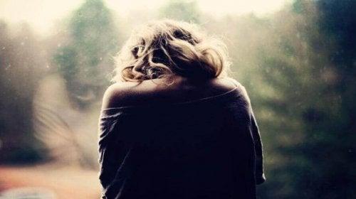 Donna di spalle con dolori dovuti alla fibromialgia