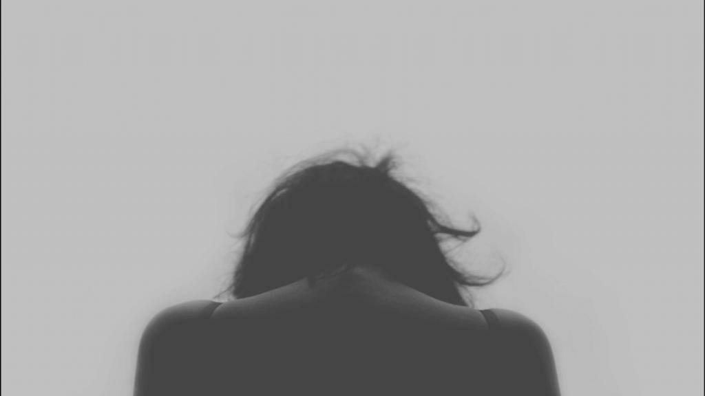 Donna di spalle con la testa chinata in basso