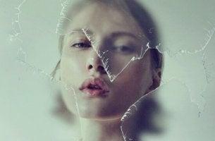 Una donna dietro ad un vetro rotto