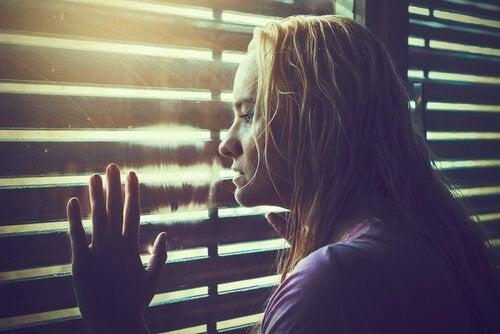 Donna che guarda dalla finestra pensando a cosa fare nella vita e come scegliere la strada giusta