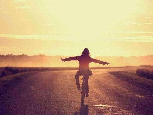 Donna in bicicletta mentre percorre una strada, felice perché non si sente persa