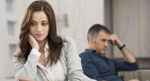 Donna preoccupata, sullo sfondo il suo partner