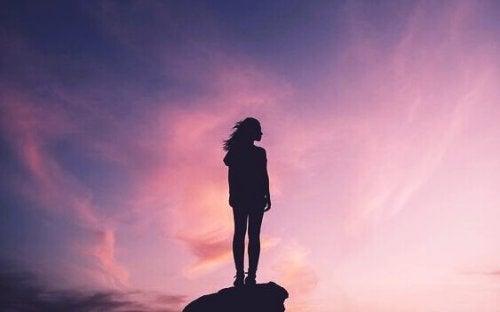 Una donna su una roccia al tramonto