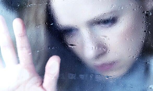 Donna triste dietro la finestra bagnata