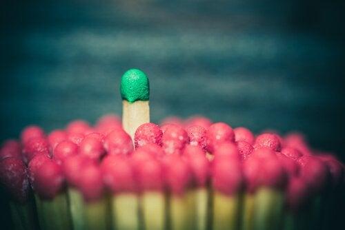 Fiammifero verde tra fiammiferi rossi