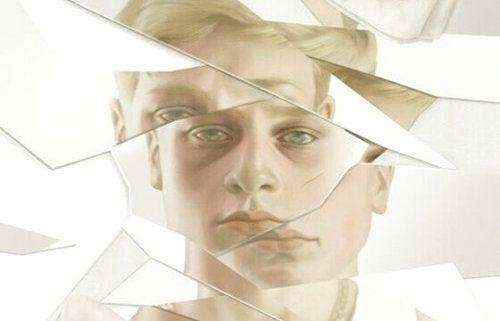 Riflesso di ragazzo in uno specchio rotto