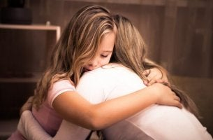 Mamma che sta abbracciando la figlia