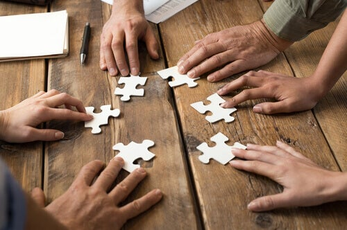 Mani di persone che stanno costruendo un puzzle