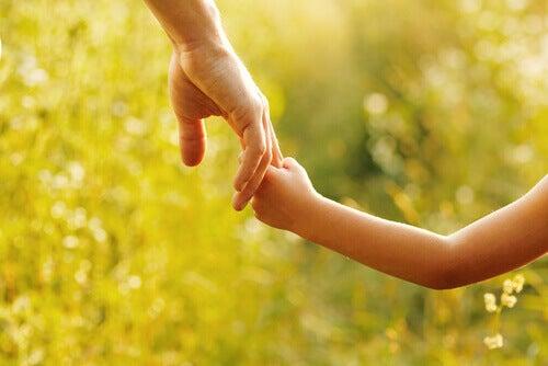 Genitore e figlio mano nella mano