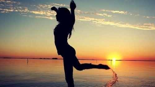 Ragazza balla felice nel mare sentendosi motivata