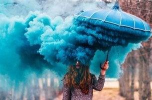 Ragazza con l'ombrello blu e fumo che rappresenta i conflitti irrisolti