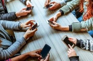 Tavolata di ragazzi con il cellulare in mano - phubbing