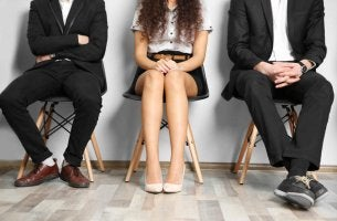 Tre persone sedute in attesa di fare un colloquio, situazione in cui la prima impressione è importante