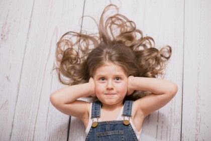 Bambina con le mani sulle orecchie