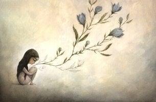 Bambina seduta e fiori