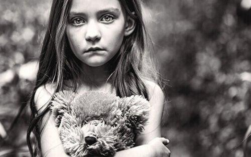 Bambina triste con un orsacchiotto