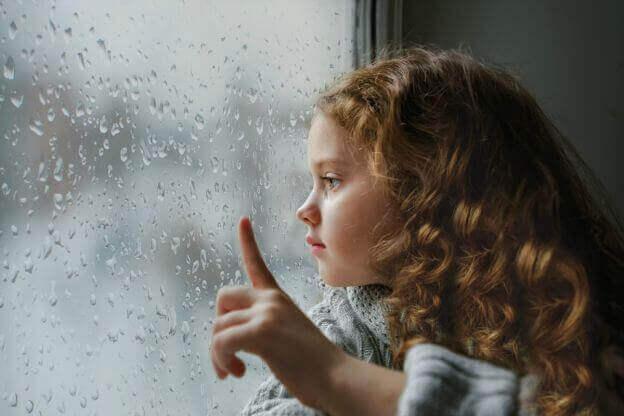 Bambina triste che guarda dalla finestra bagnata