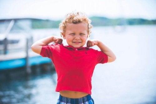 Bambino biondo con le braccia flesse per mostrare i muscoli