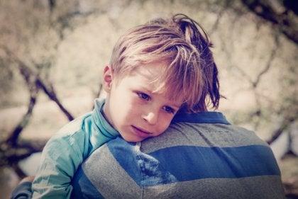 Bambino triste in braccio al padre