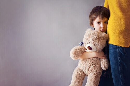Bambino triste che tiene un orsacchiotto ed è aggrappato a sua madre