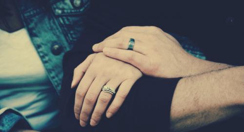 Donna aggrappata al braccio del suo partner, come simbolo della sintonia di coppia