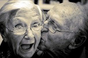 Coppia di anziani felici che si danno un bacio